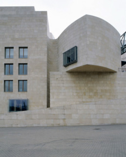 Guggenheim Art Museum in Bilbao Spain by Architect Frank Gehry, photographed by Larry Speck. Exterior, back, behind, limestone siding.